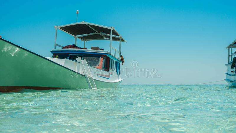 A traditional boat fishing anchored on sea sore with shallow sea with clear and transparent water royalty free stock photos