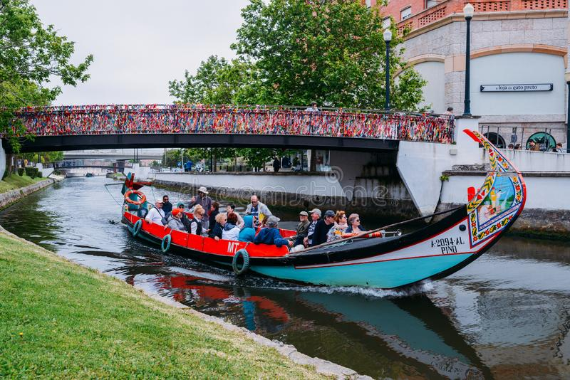 Traditional boat, Moliceiro, transporting tourists passing under bridge covered in confetti on canal at Aveiro, Portugal royalty free stock photos