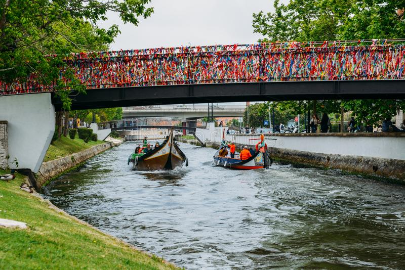 Traditional boat, Moliceiro, transporting tourists passing under bridge covered in confetti on canal at Aveiro, Portugal royalty free stock photography