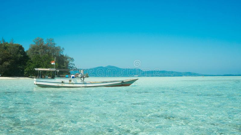 Traditional boat transportation on the shallow sea with transparent clear and island in distance stock photos