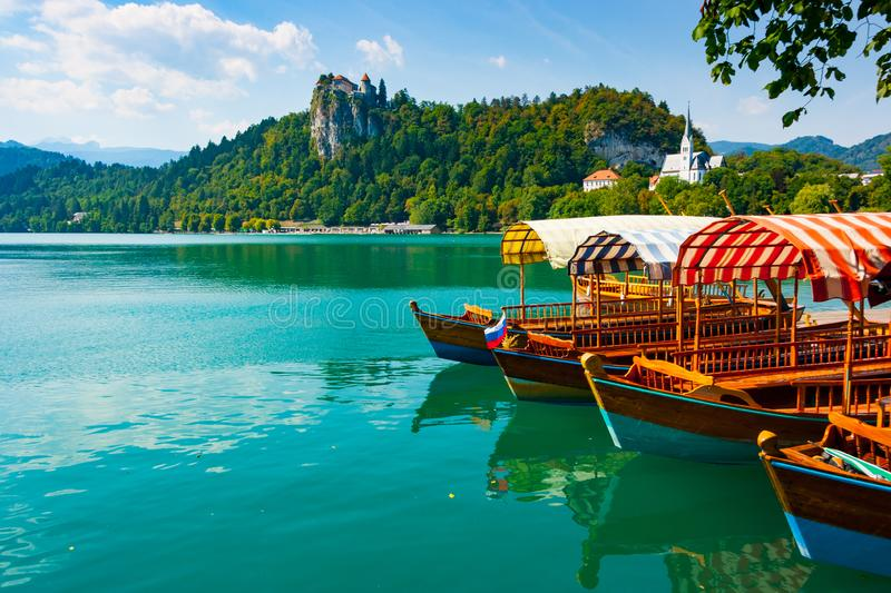 Traditional boats on Bled lake. Traditional pletna boats on the green waters of Lake Bled with Bled Castle cliff on the background, Upper Carniola, Slovenia stock photography
