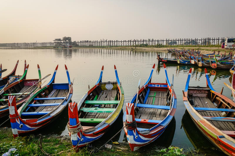 Wooden boats on lake in Mandalay, Myanmar. Traditional boats waiting tourists on lake at sunset in Mandalay, Myanmar royalty free stock image