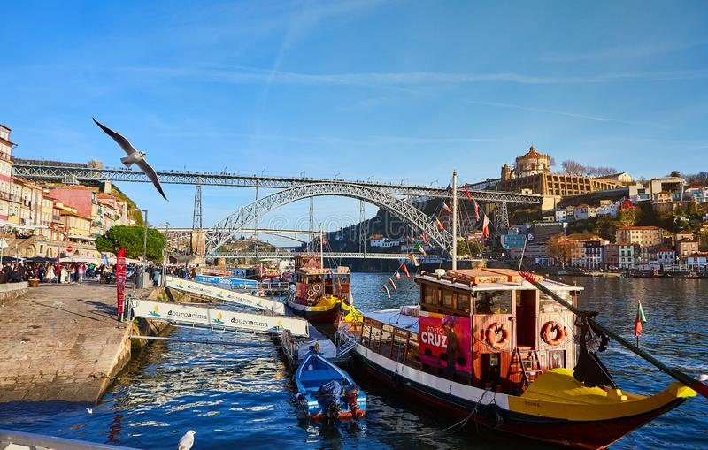 09 of December, 2018 - Porto, Portugal: Traditional boats with wine barrels on Douro river in old town with background of Dom Luis royalty free stock photography