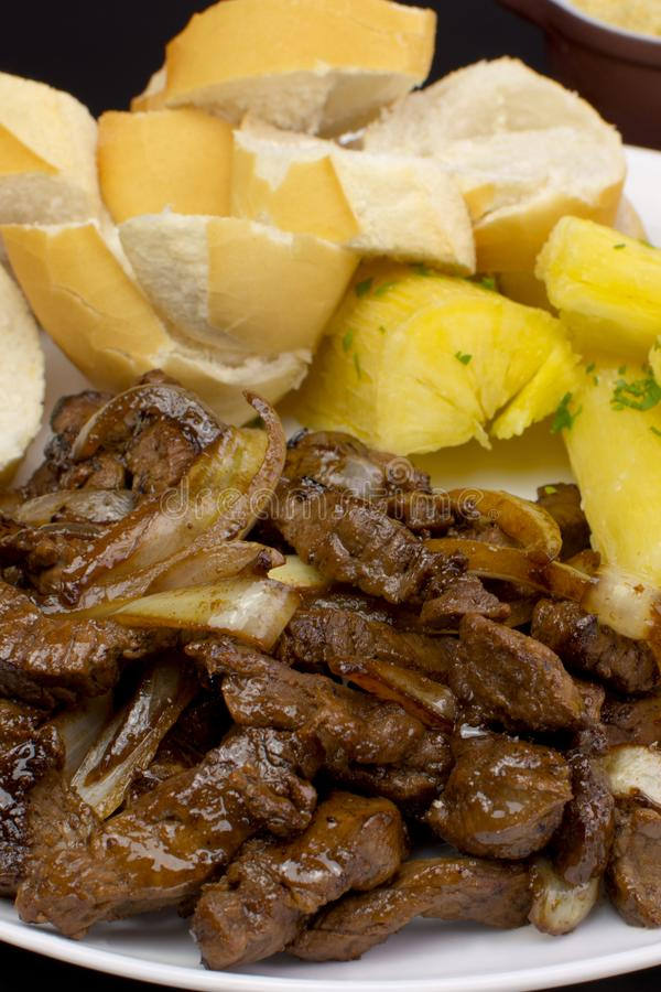 Traditional Brazilian pub food striploin with onions vertical stock photo