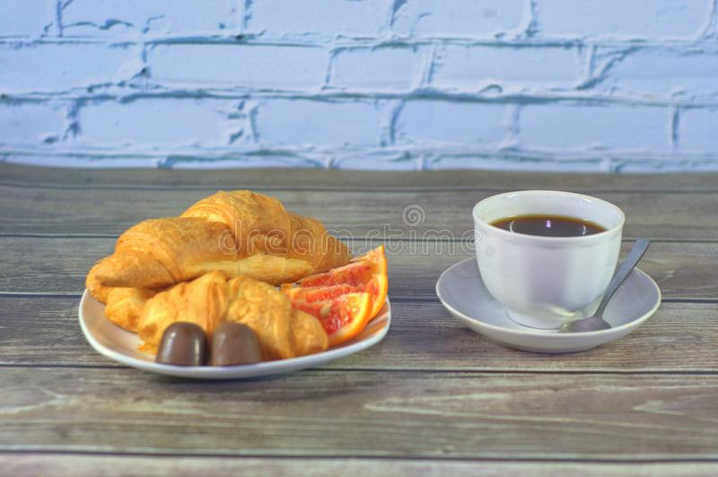 Traditional breakfast, a cup of black coffee and croissants with orange slices and chocolates. Close-up stock photo