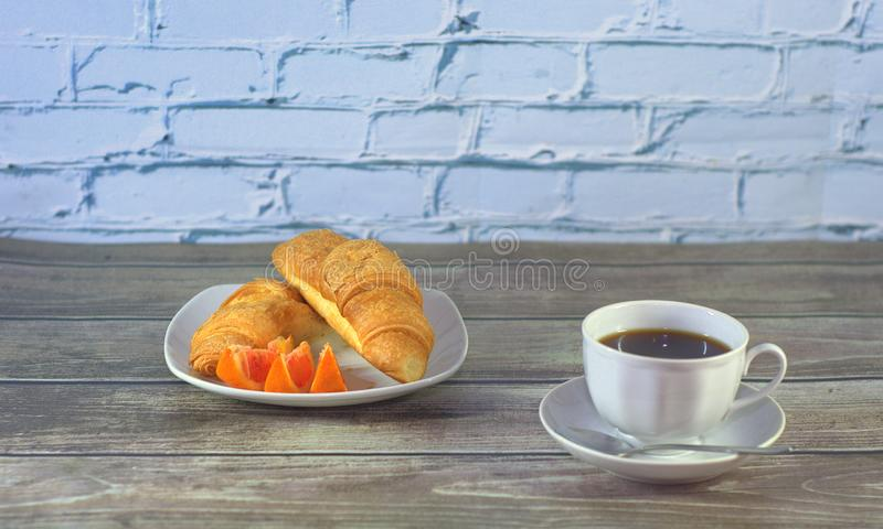 Traditional breakfast, a cup of black coffee, croissants, slices and orange on the table. Close-up royalty free stock photography