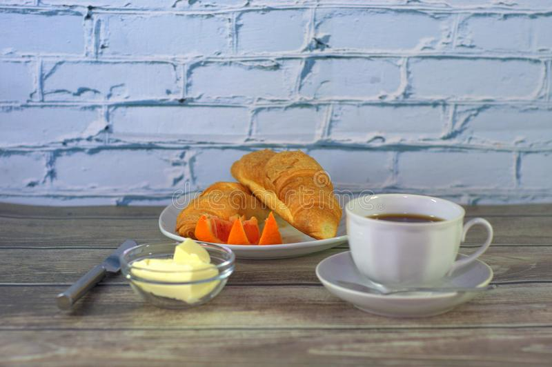 A traditional breakfast, a cup of black coffee, two croissants with butter and orange slices. Close-up stock photography