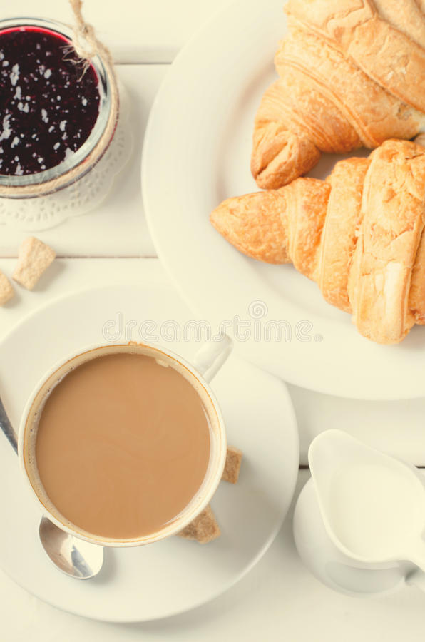Traditional breakfast with fresh croissants and coffee on white wooden background. royalty free stock photography