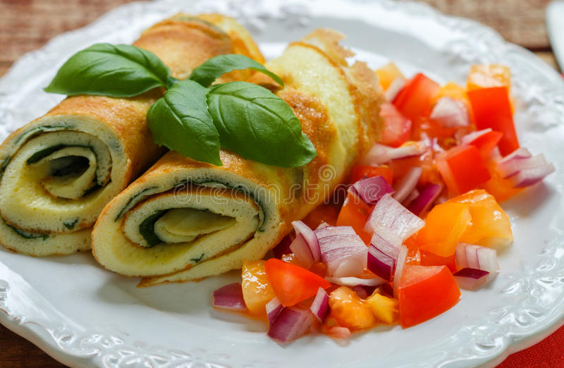 A traditional Breakfast. Omelette with spinach and a fresh tomato salad, red onion and Basil. Roll scrambled eggs stock photos