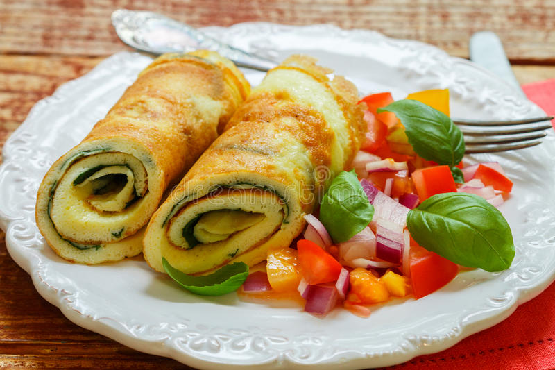 A traditional Breakfast. Omelette with spinach and a fresh tomato salad, red onion and Basil. Roll scrambled eggs royalty free stock photos