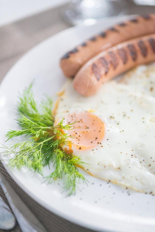 Traditional breakfast with sausages, fried eggs with ground black pepper and bread. Traditional breakfast with sausages, fried eggs, seasoned with ground black stock photography