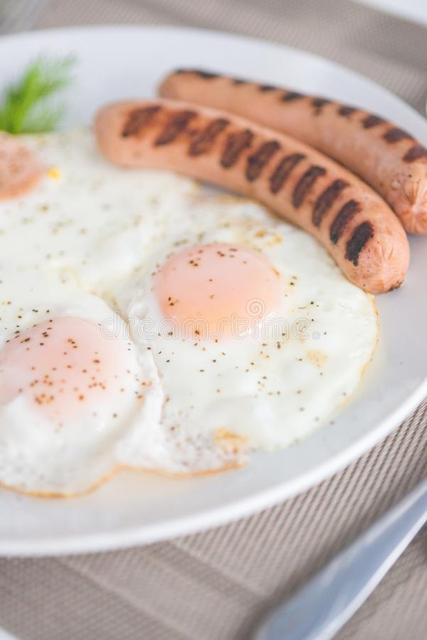 Traditional breakfast with sausages, fried eggs with ground black pepper and bread. Traditional breakfast with sausages, fried eggs, seasoned with ground black royalty free stock photography