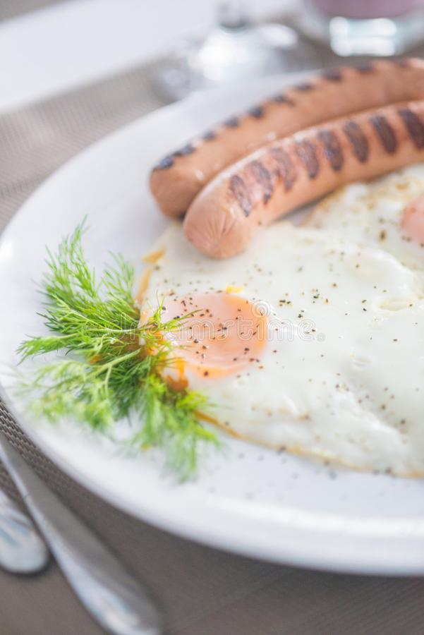 Traditional breakfast with sausages, fried eggs with ground black pepper and bread. Traditional breakfast with sausages, fried eggs, seasoned with ground black stock photo