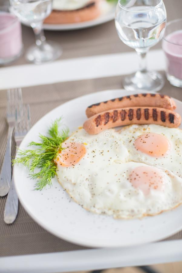 Traditional breakfast with sausages, fried eggs with ground black pepper and bread royalty free stock photography