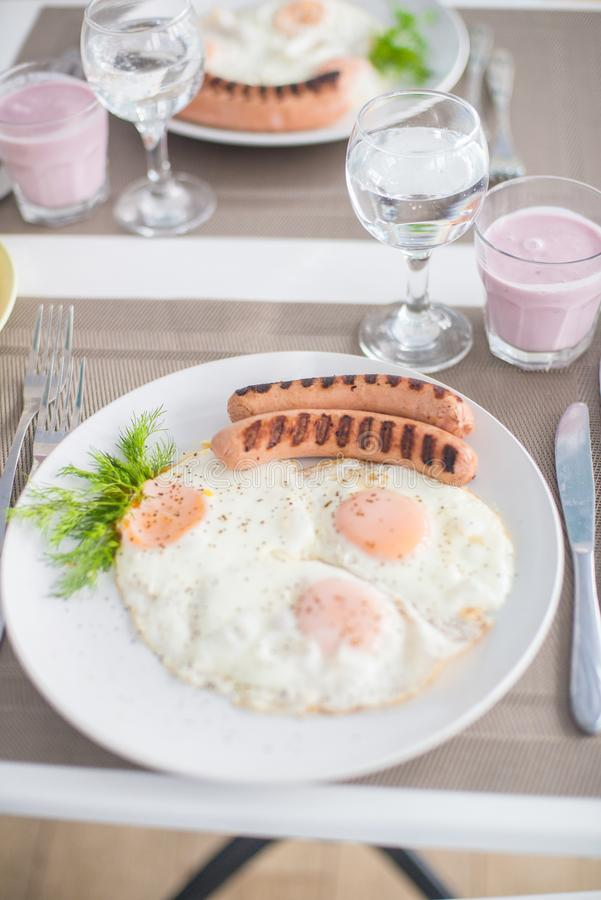 Traditional breakfast with sausages, fried eggs with ground black pepper and bread royalty free stock image