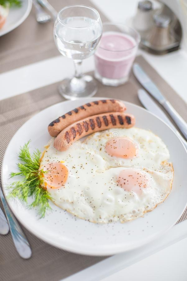 Traditional breakfast with sausages, fried eggs with ground black pepper and bread. Traditional breakfast with sausages, fried eggs, seasoned with ground black stock images