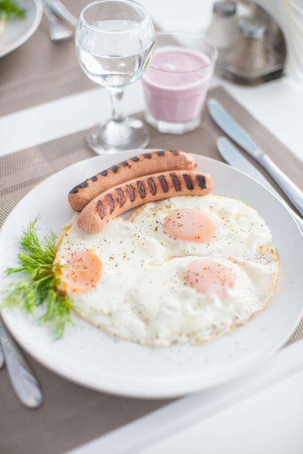 Traditional breakfast with sausages, fried eggs with ground black pepper and bread. Traditional breakfast with sausages, fried eggs, seasoned with ground black royalty free stock photos