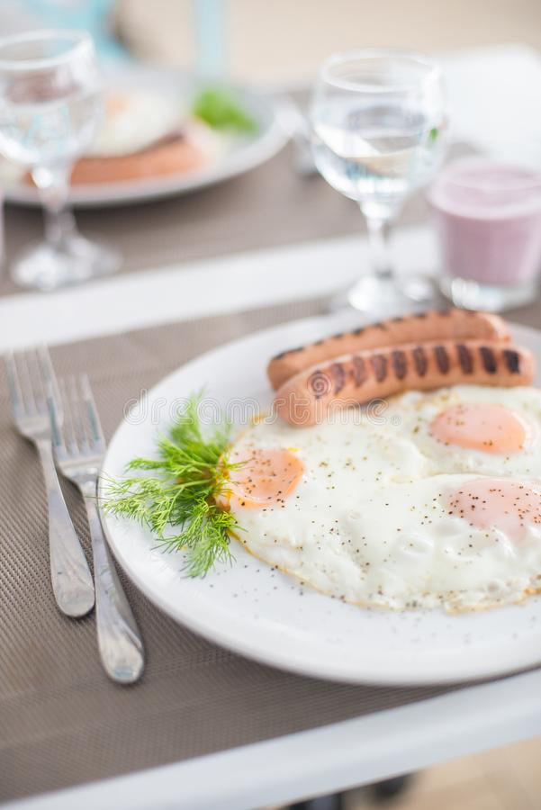 Traditional breakfast with sausages, fried eggs with ground black pepper and bread. Traditional breakfast with sausages, fried eggs, seasoned with ground black royalty free stock images