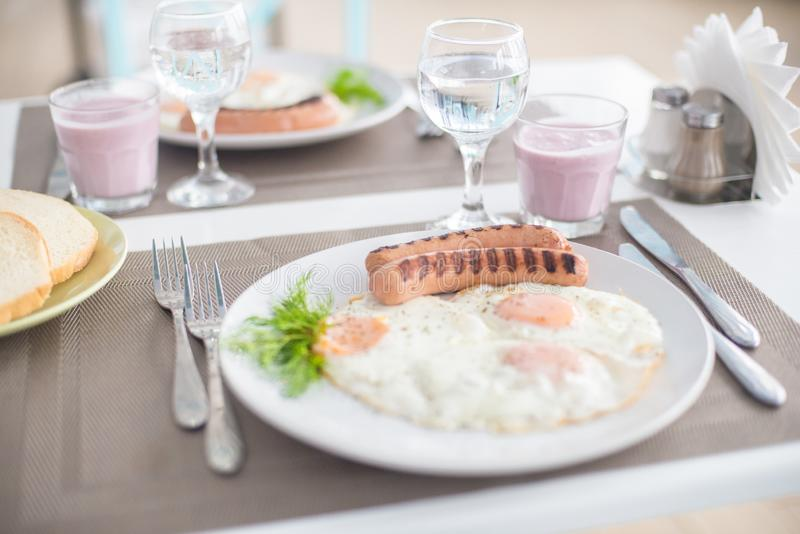 Traditional breakfast with sausages, fried eggs with ground black pepper and bread royalty free stock photos