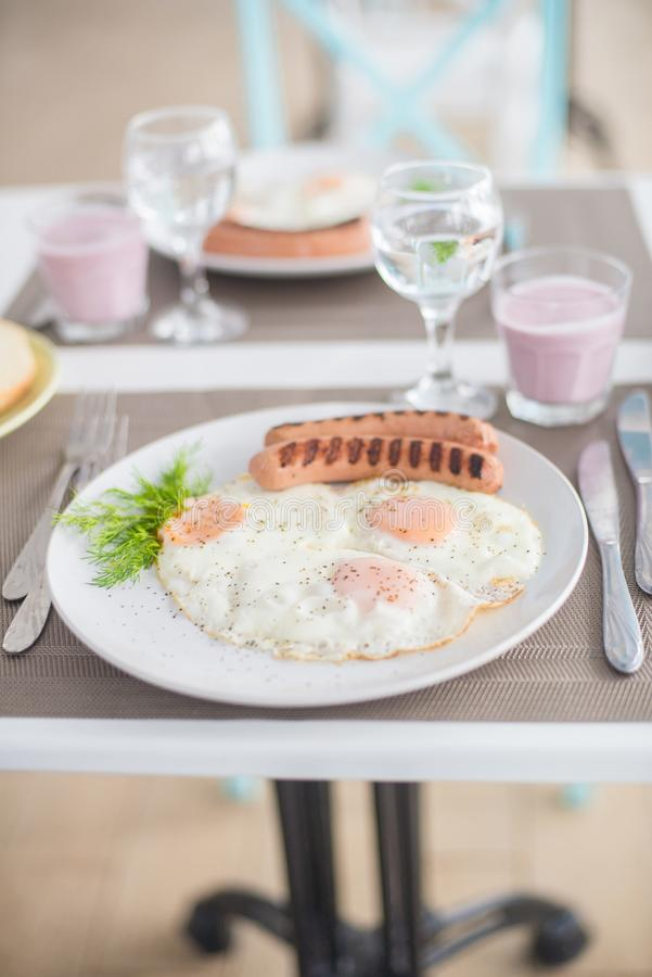 Traditional breakfast with sausages, fried eggs with ground black pepper and bread. Traditional breakfast with sausages, fried eggs, seasoned with ground black royalty free stock image