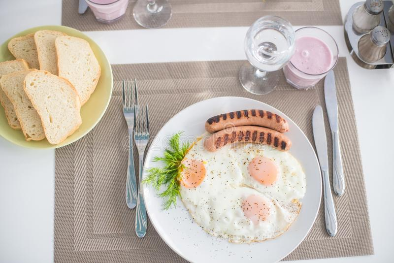 Traditional breakfast with sausages, fried eggs with ground black pepper and bread stock photography