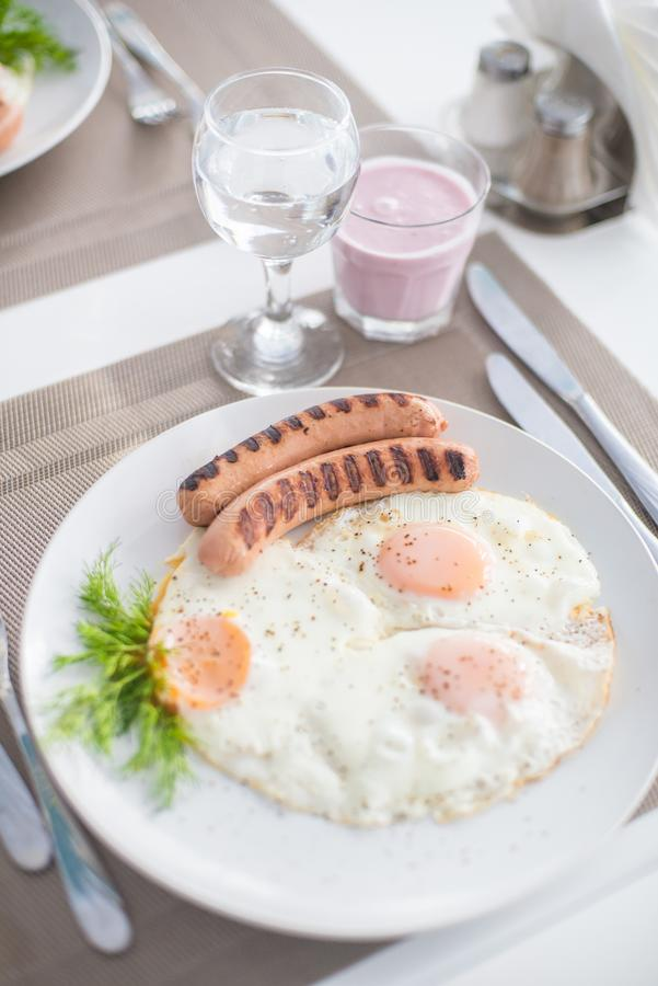 Traditional breakfast with sausages, fried eggs with ground black pepper and bread stock photo
