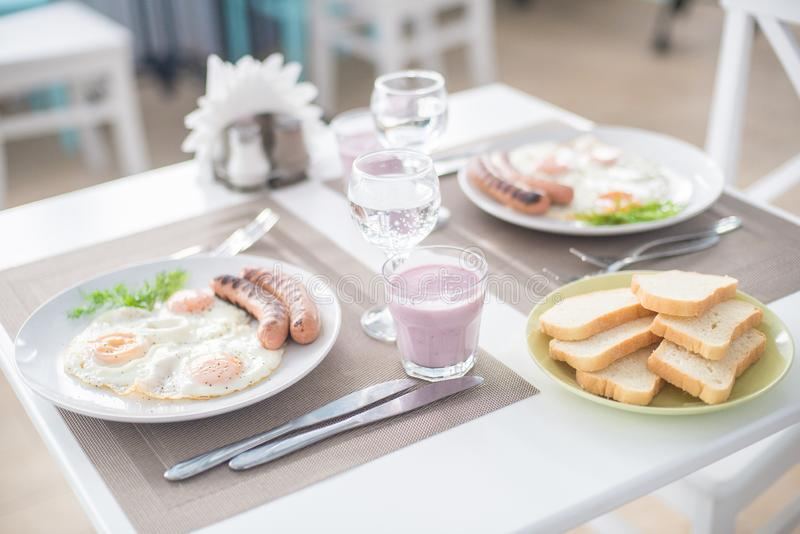 Traditional breakfast with sausages, fried eggs with ground black pepper and bread stock image
