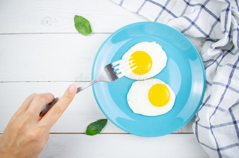 Traditional breakfast of two fried eggs. Blue plate with eggs on the background of a white wooden table. Concept image stock photo