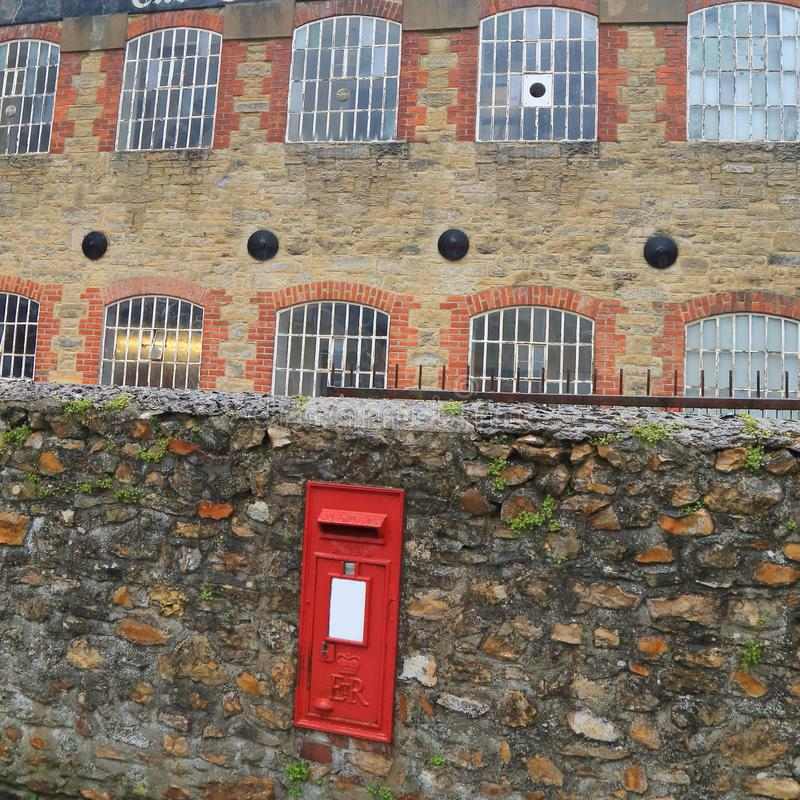 Traditional British red post box. Embedded in a stone wall in Axminster, Devon stock images
