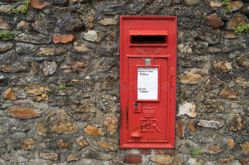 Traditional British red post box. Embedded in a stone wall in Axminster, Devon stock photos