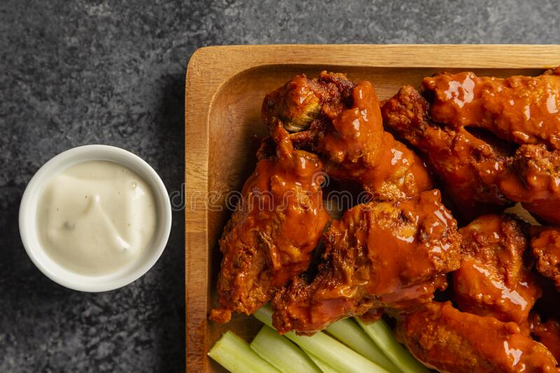 Traditional Buffalo style chicken wings. On a wooden plate with celery and ranch dressing royalty free stock images
