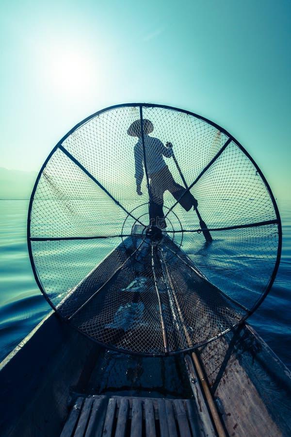 Traditional Burmese fisherman at Inle lake. Myanmar travel attraction landmark - Traditional Burmese fisherman with fishing net at Inle lake in Myanmar famous stock image