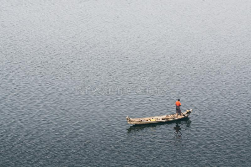 Traditional Burmese fisherman in a wooden boat on Irrawaddy river close to Bagan, Myanmar royalty free stock photo