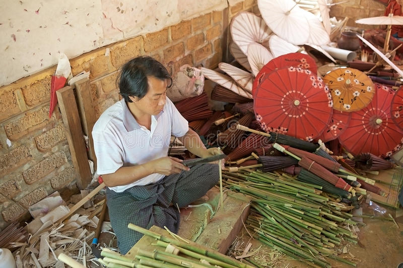 Traditional Burmese parasol. Burmese man is making the traditional burmese parasola at the Pindaya workshop, Myanmar or Burma. In Burmese tradition the parasol stock photos