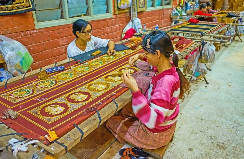 Traditional Burmese tapestries, Mandalay, Myanmar. MANDALAY, MYANMAR - FEBRUARY 21, 2018: Artisans embroider large tapestry with traditional Burmese patterns royalty free stock photos
