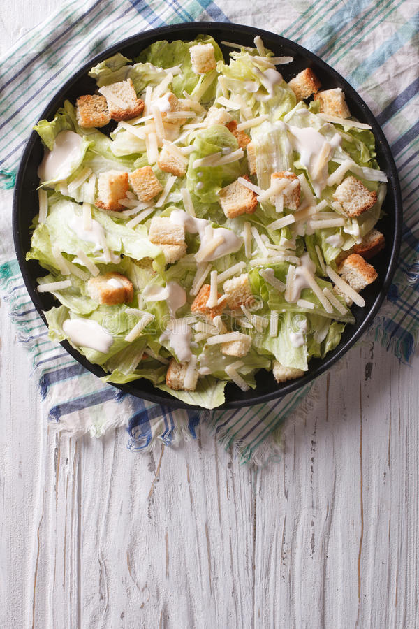 Traditional Caesar salad on a plate. vertical top view stock photos