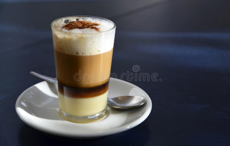 Traditional Canarian coffee Barraquito with separated layers of milk condensed and liquor on a dark background. Selective focus royalty free stock photo