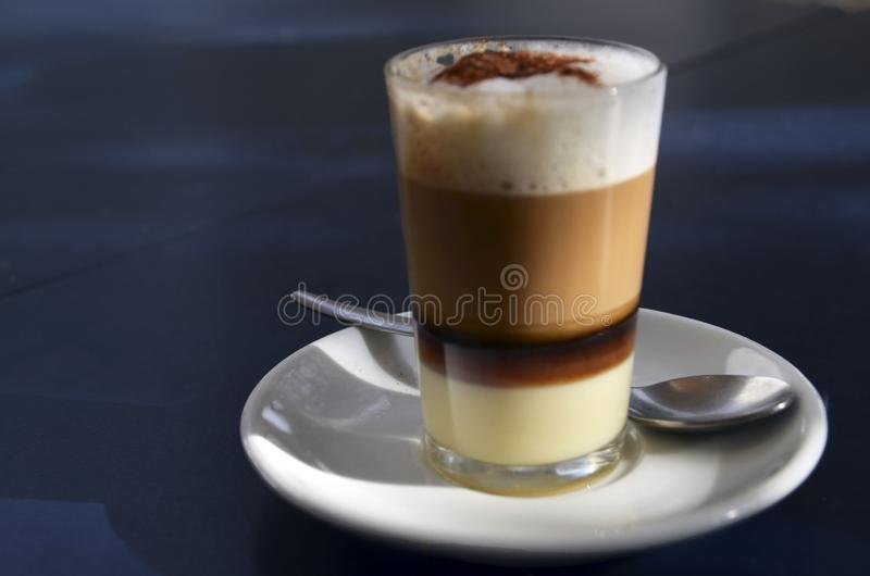 Traditional Canarian coffee Barraquito with separated layers of milk condensed and liquor on a dark background. Selective focus stock photography