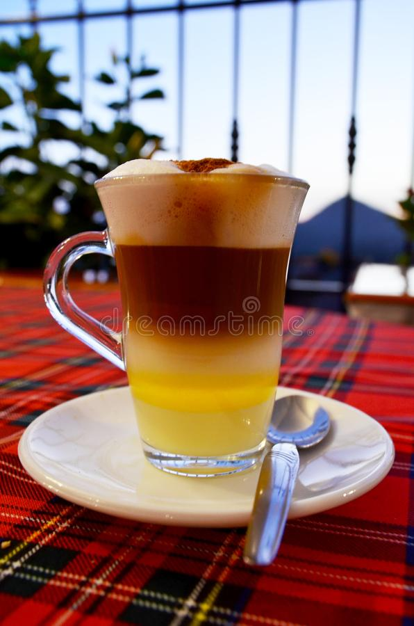 Traditional Canarian coffee Barraquito with separated layers of milk condensed and liquor on the terrace of cafe in Tenerife,Canar. Y Islands,Spain.Selective stock photography
