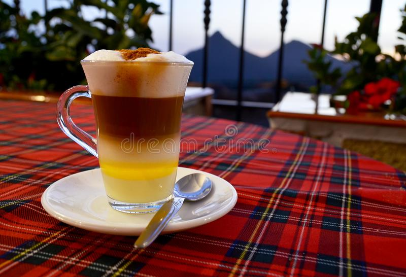 Traditional Canarian coffee Barraquito with separated layers of milk condensed and liquor on the terrace of cafe in Tenerife,Canar. Y Islands,Spain.Selective royalty free stock image