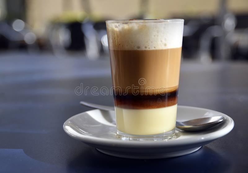 Traditional Canarian coffee Barraquito with separated layers of milk condensed and liquor on the terrace of cafe in Tenerife,Canar. Y Islands,Spain.Selective royalty free stock images
