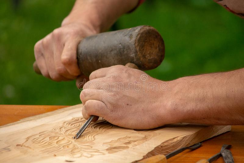Traditional carpenter close up working hands with carpeting tools. royalty free stock images