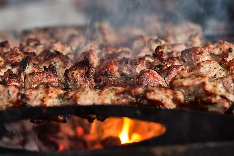 Traditional Caucasian BBQ shashlik grilled meat on sticks being cooked on open fire with smoke, close up view royalty free stock image