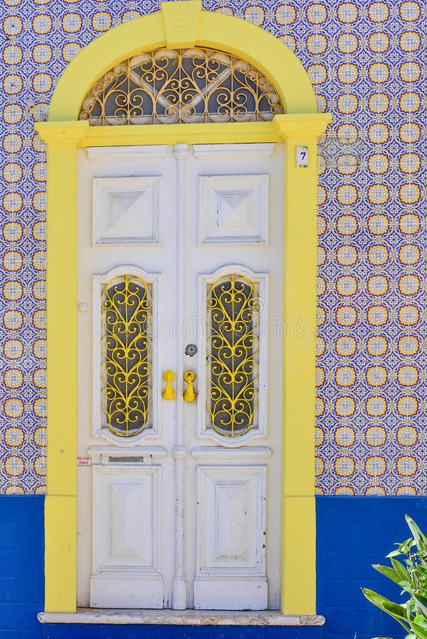 Traditional ceramic tile Portuguese house with a yellow door in bright blue, white and yellow colors stock photos