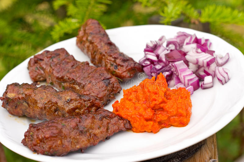 Traditional cevapcici with ajvar paste. And red onion royalty free stock image
