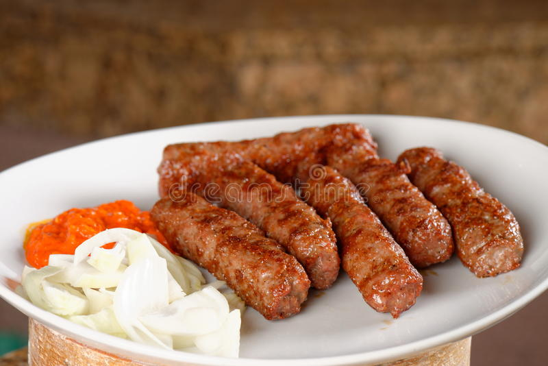Traditional cevapcici with ajvar paste. And onion royalty free stock photography