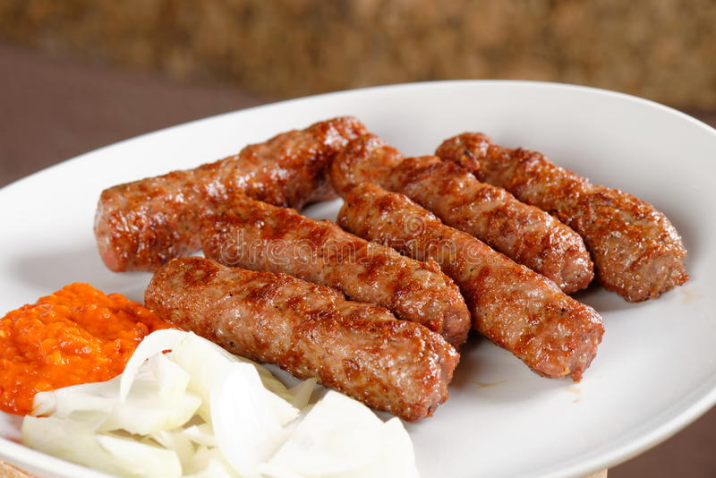 Traditional cevapcici with ajvar paste. And onion stock photo