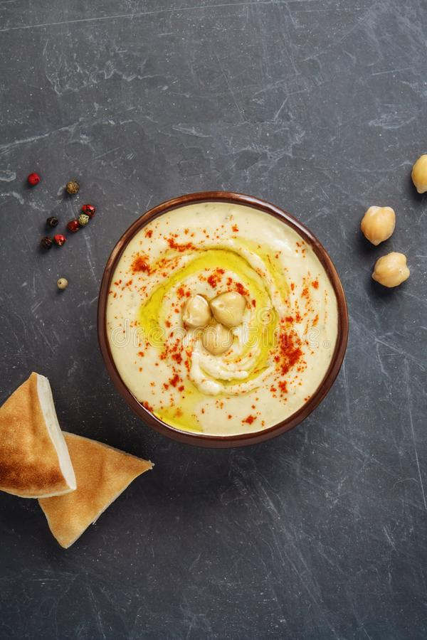 Traditional chickpea hummus bowl with pita flatbread, chickpeas and spices on gray background. Healthy mediterranean vegetarian dip. Top view, flatlay, copy royalty free stock photography