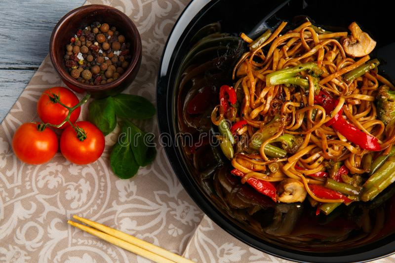 Traditional Chinese dish on a round plate, rice noodles, cabbage green cabbage and fried vegetables, red cherry tomatoes stock photos