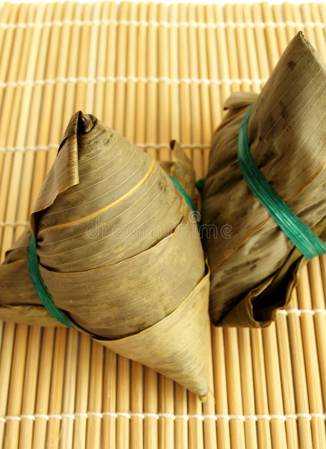 Traditional chinese dumplings. Two traditional chinese dumplings wrapped in dried bamboo leaves. Made from glutinous rice and a mixture of meat stuffing such as stock photo